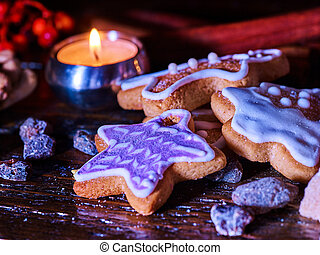 Candle light table with Christmas gingerbread cookies .