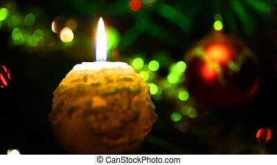 candle lit in front of festive lights Christmas tree