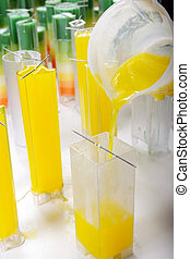 Candle manufacture , pouring colorful molten yellow wax into...
