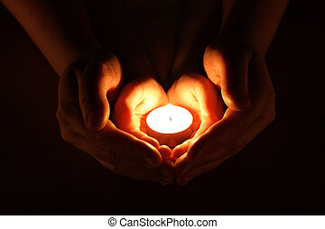 candle on a palm on a dark background