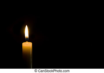 candle on black - a single tall lit candle on a black ...