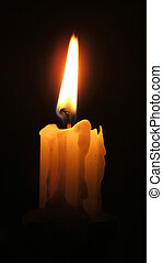 Candle glows on a black background