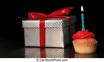 Candle on cupcake blown beside gift on black background