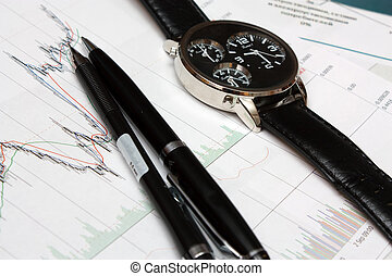 candle stick chart and watch, pen.