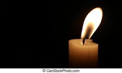 Candle - A single close up candle slowly flickers with a...