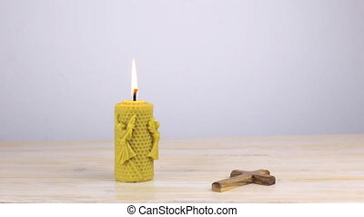 Candle with orthodox cross on wooden table
