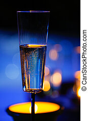 Candlelit champagne glass beside a jacuzzi