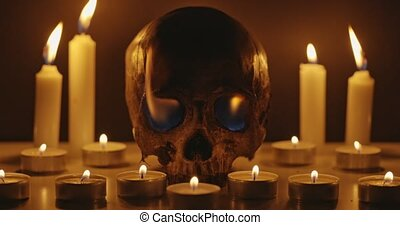 Candles and human skull in darkness close up footage