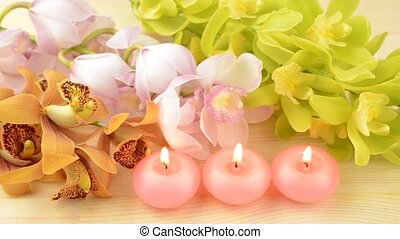 Candles and orchid flowers - Three pink candles in front of...