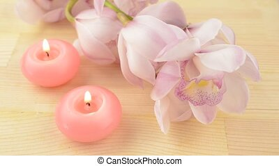 Candles and orchid flowers - Two pink candles beside pale...