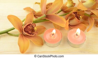 Candles and orchid flowers - Two tin candles beside brown...