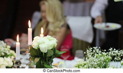 candles and white roses on the festive table