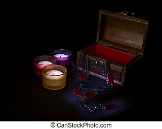 Three colored candles stand next to an open wooden chest