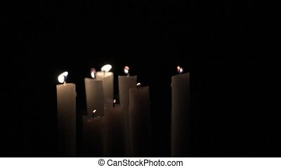 Candles blow out in the darkness - A group of eight candles...