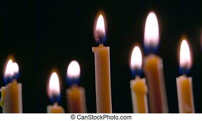 Candles burn, a beautiful orange flame. Black background....