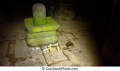 Candles on the stone floor of a Hindu temple, in front of a Lingam and Yoni, symbols of the god Shiva and the goddess Shakti. Video UltraHD