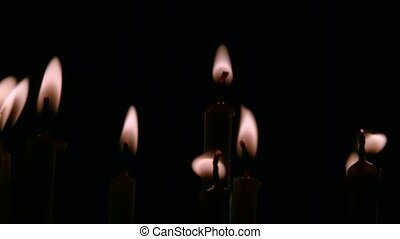 Candles burn in a dark temple. Black background. Close up