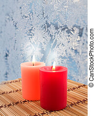 candles burn on a background of frozen window