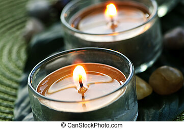 Burning candles in glass holders on green leaf