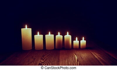 Candles burning in dark - Candles standing in line burning...