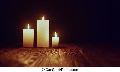 Candles burning in dark - Zoom in rack focus video of three...