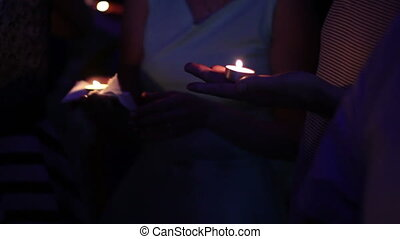 candles burning in the hands of women at dark