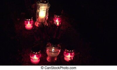 Candles burning on graves at cemetery at night. All Hallows...
