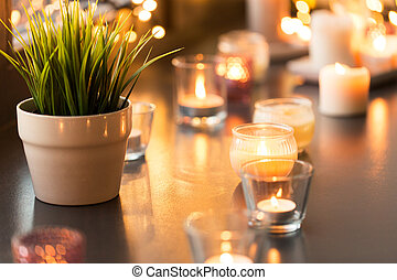 candles burning on window sill with garland lights