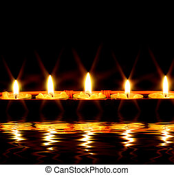 Candles by the water - row of candles reflected in the water