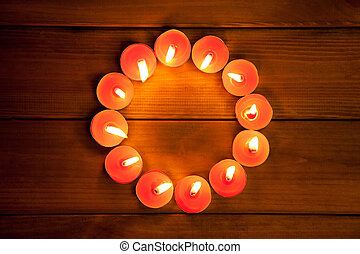 candles cirlce shape on warm golden wood - candles glowing...