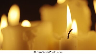Candles glowing against dark background closeup footage