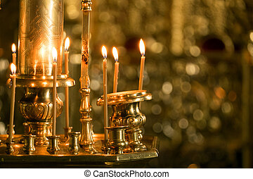 Candles in a church - Burning candles in a church on a...