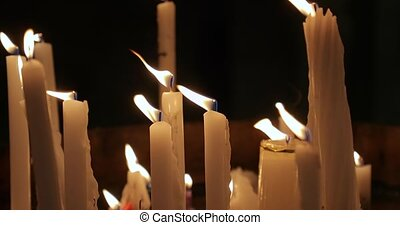 Candles burning on a church altar in dim light