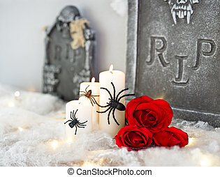 Candles in Halloween decoration and red roses