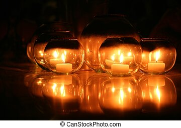 Candles in round glasses over black background