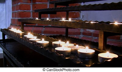 Candles in the church - View of rows of candles glowing in a...