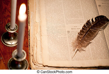 Candles in the dark near book and feather