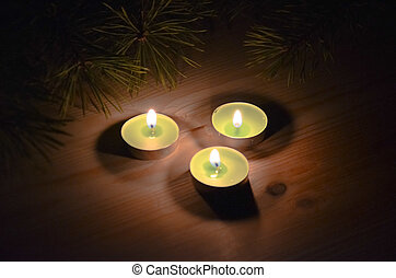 candles in the dark on the wooden background next to a fir tree branches