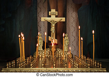candles in the darkness against the Orthodox cross
