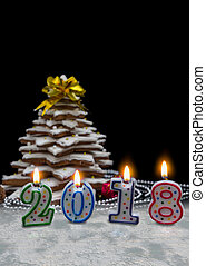 Candles in the form of 2018 new year near homemade gingerbread Christmas tree with decorations on dark background