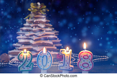 Candles in the form of 2018 new year near homemade gingerbread Christmas tree with decorations on dark background during the snow