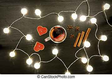 Candles in the shape of a heart, mulled wine with spices, cinnamon and anise. Rattan lanterns on black wooden table, top view
