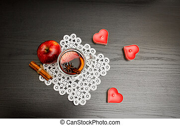 Candles in the shape of a heart, mulled wine with spices on a lace napkin, apple and cinnamon sticks. Black wood background, top view