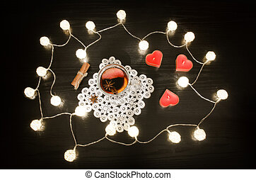 Candles in the shape of a heart, mulled wine with spices on a lacy napkin, cinnamon. Rattan lanterns on black wooden table, top view