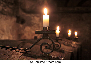 Candles in wine-cellar on old wine barrels