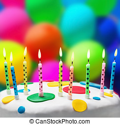 candles on a birthday cake on the background of balloons