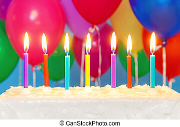 Candles on a cake with balloons in background - Candles...