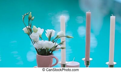 Candles on the background of blue water