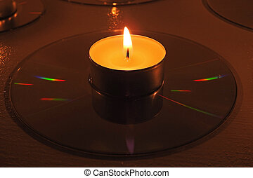 Candles placed on compact disks. Candle composition with CD.