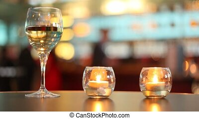 candles putted inside glass and goblet filled with wine...